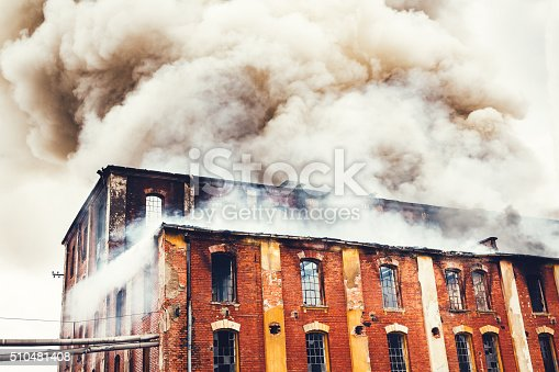 Grey clouds of smoke swirling out of an old abandoned red-brick industrial building.