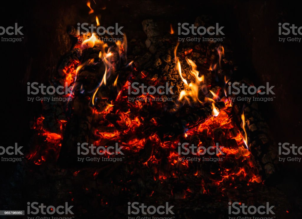 Fire in fireplace Fire in fireplace with coal and firewood Brightly Lit Stock Photo