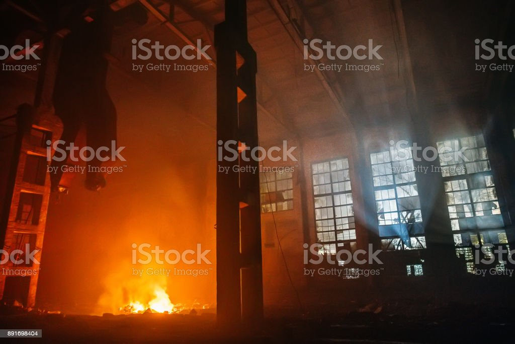 Fire in large hall of factory or warehouse at night. Huge flame of red and yellow fire and blue light from windows stock photo