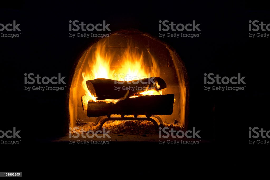 Fire in outdoor fireplace at night stock photo