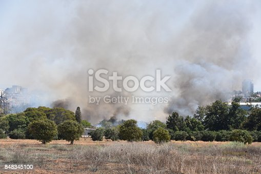 istock Fire in the field near the city 848345100