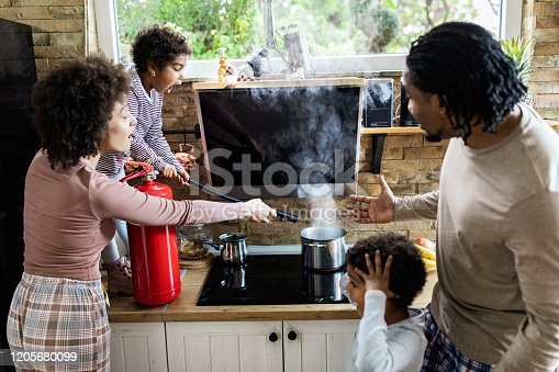 African American family using fire extinguisher while spraying smoke from a saucepan in the kitchen. Focus is on shocked girl.