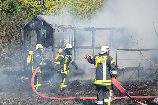 fire is extinguished Fuerstenwalde, Germany - April 21, 2011: Fully equipped german firefighters with respiratory devices during Fire Fighting. The fire destroyed a holiday home within minutes. The firefighters are fire department Fuerstenwalde. russian dacha stock pictures, royalty-free photos & images