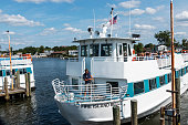 Bay Shore, New York, USA - 25 August 2018: The Fire Island Belle Ferry boat leaving the Bay Shore Docks brining people on vacation and to the beach on Fire Island.