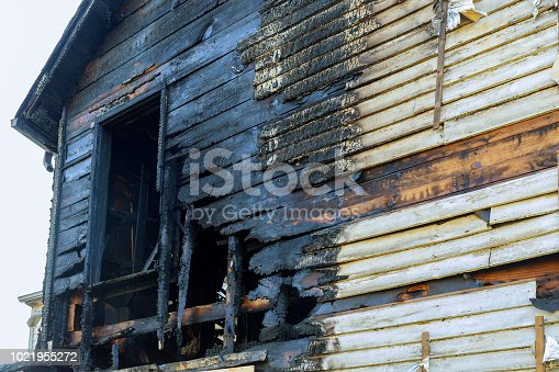 1015604978 istock photo Fire line in front of a destroyed home. burnt house after fire 1021955272