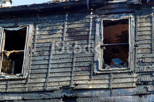 1015604978 istock photo Fire line in front of a destroyed home. burnt house after fire 1021955316