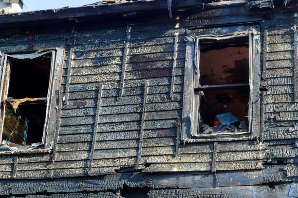 brand raden framför en förstörda hem. brända hus efter brand - brand sotiga fönster bildbanksfoton och bilder