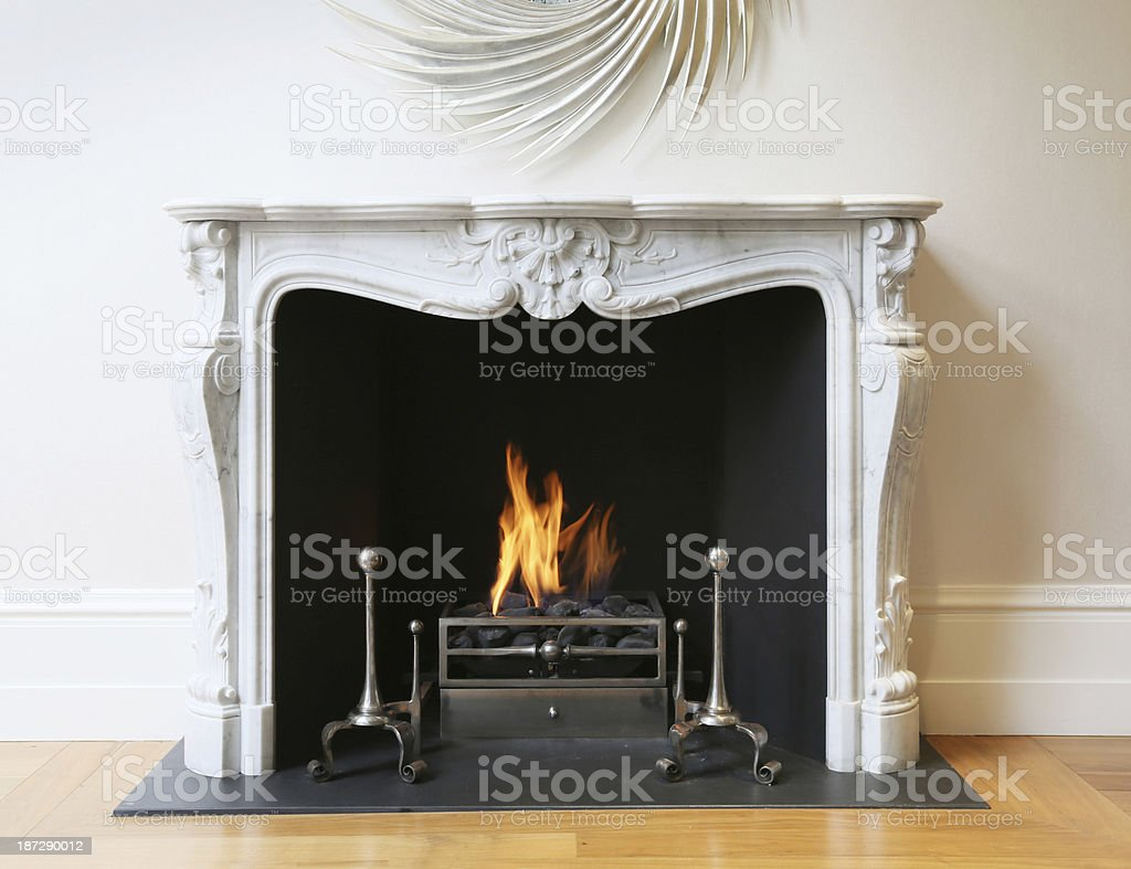 Fire lit in an embellished white fireplace in a fancy home stock photo