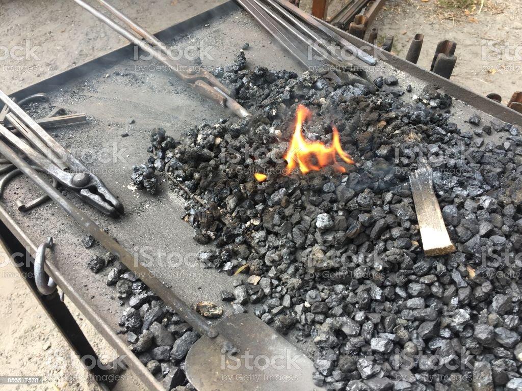 Fire, live coals and blacksmith's tools stock photo