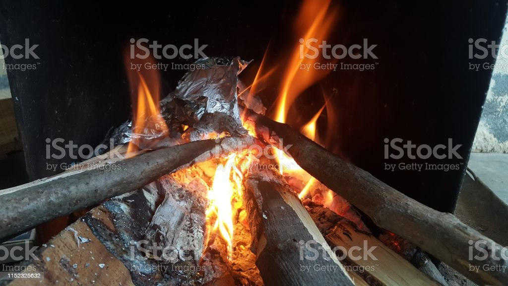 Fire on logs in fire pot with embers and burning coal. Bonfire with...