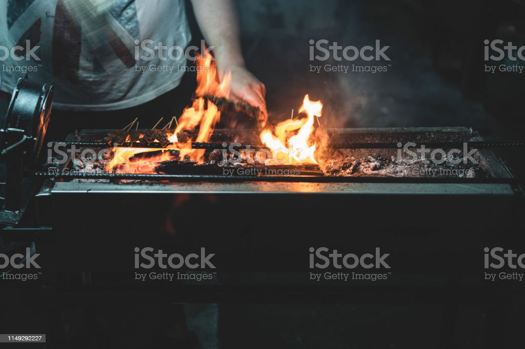 Fire on the Barbecue The fire on the barbecue on the street stall at the night. Ash Stock Photo