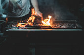 The fire on the barbecue on the street stall at the night.