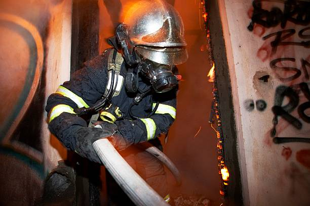 Fire Fireman extinguishing fire inside an old house in Prague. smoke jumper stock pictures, royalty-free photos & images