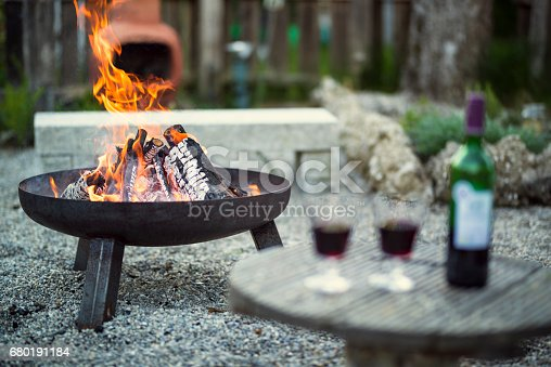 fire pit in a garden with two galss of red wine in the foreground