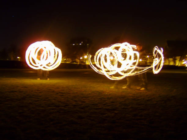 Fire poi performers creating yellow light trails stock photo