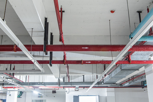 Fire protection sprinkler system with red pipes is placed to hanging from the ceiling