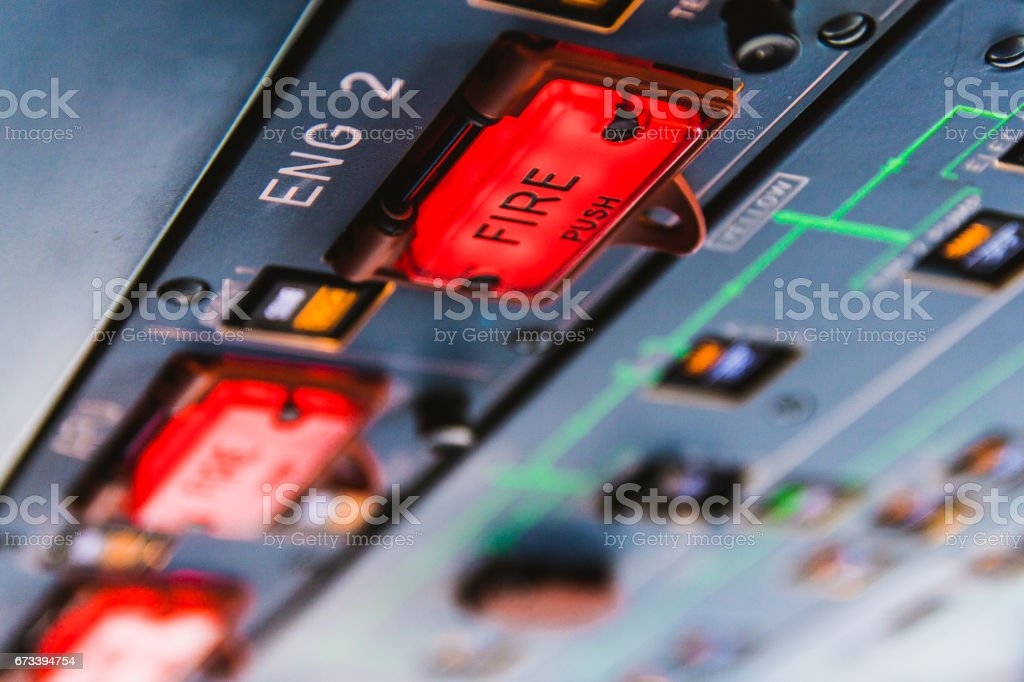 Fire pushbuttons and warning lights on the overhead panel in an airliner cockpit. Bright red warning lights come on when a fire is detected in one of the engines or the APU. stock photo