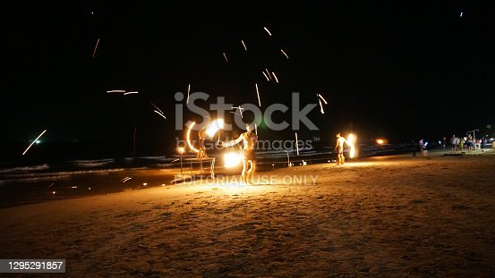 Fire show on the beach of Chang island, Thailand. Half-naked guys juggle fire rods. A lot of sparks fly in different directions. Waves from the sea beat against the shore. People watch and admire.
