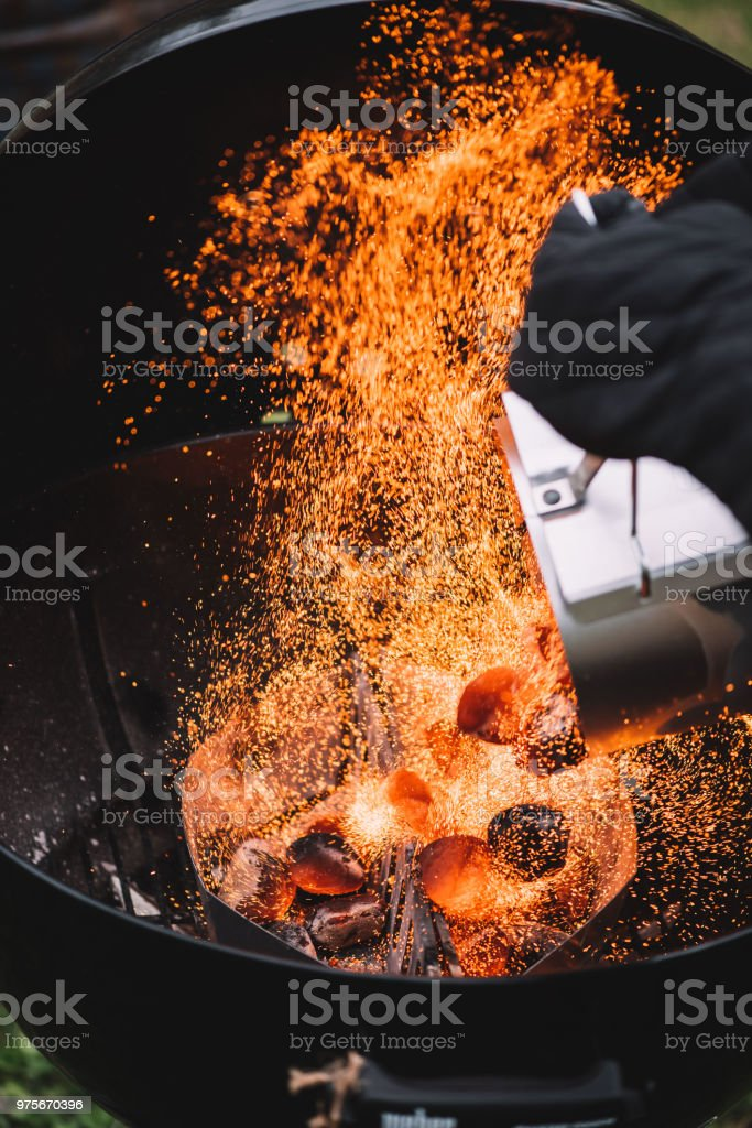 Fire sparks caught up in the moment of putting hot wood charcoal from...