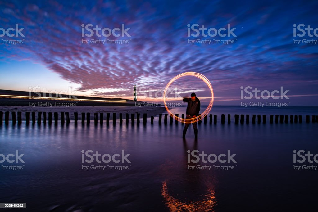 Fire spinning on the beach stock photo