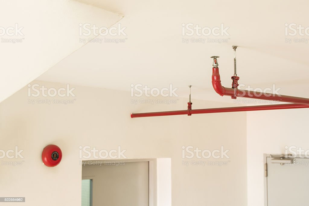 Fire sprinkler and red pipe hanging on ceiling of buliding stock photo