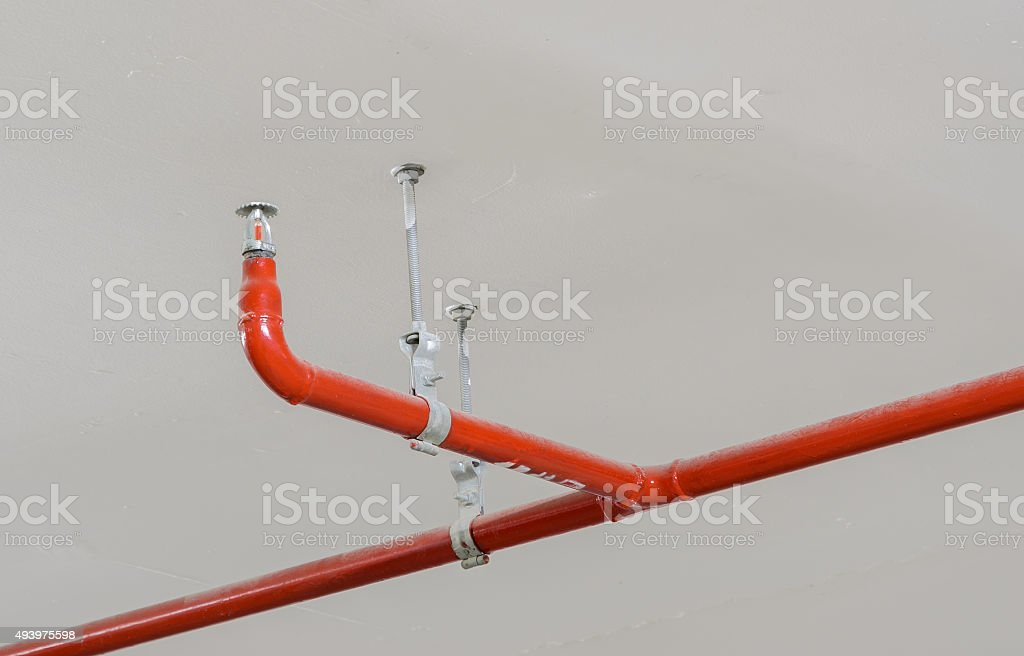Fire sprinkler and red pipe on ceiling stock photo