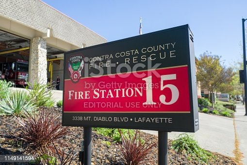 Lafayette, California, United States - April 18, 2019:  Close-up of sign for Fire Station 15 with engines visible in background, part of the Contra Costa County Fire and Rescue service, Lafayette, California, April 18, 2019
