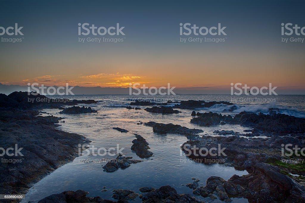 fire sunrise on the sea beach, rocky shore stock photo