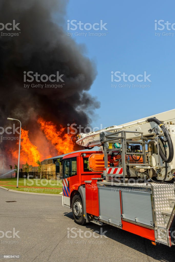 Fire engine or fire truck in front of a large fire in an industrial...