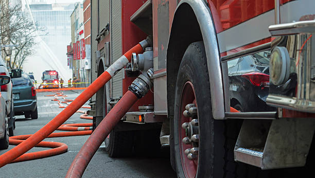 Fire truck close-up with hoses Firefighters Fire Men Fighting Fire Fire truck hoses stretched out over city street to burning building with water flowing several stories high and team of firemen fighting fire in the background, selective focus on fire truck and fire fighting hose smoke jumper stock pictures, royalty-free photos & images