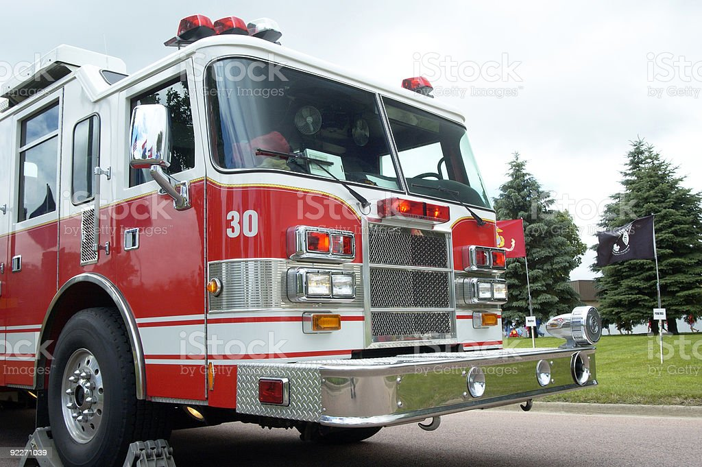 A fire truck parked on the road with stoppers around a wheel stock photo