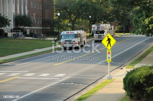 istock Fire trucks at university building 182380145
