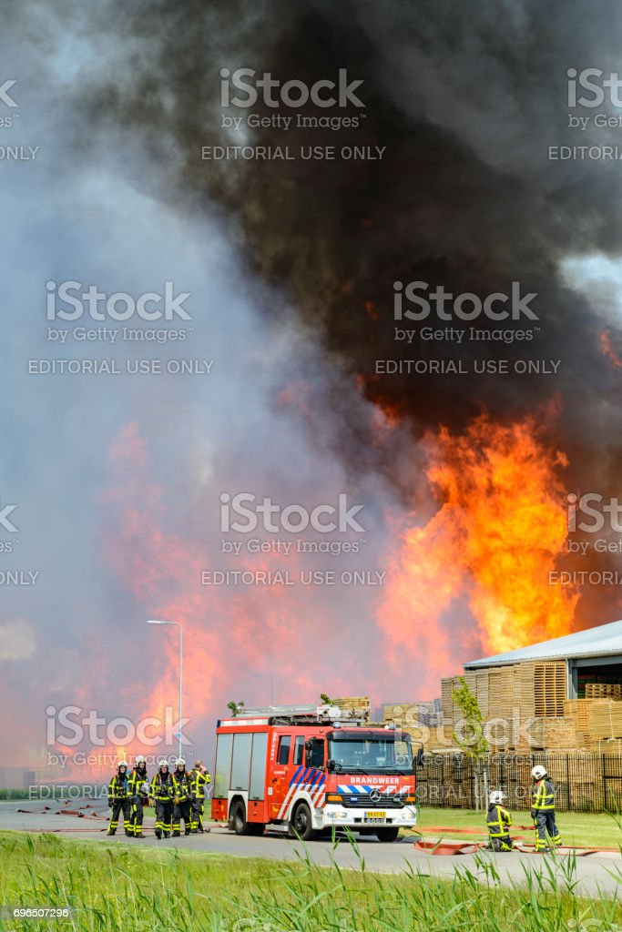 Fire trucks in front of a large fire in a Pallet factory in an...