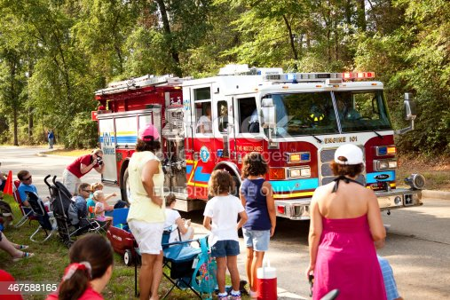 istock Fire trucks in July 4th parade. Local community. Spectators watching. 467588165