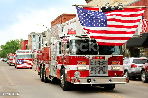 istock Fire Trucks with American Flags at Small Town Parade 477872074