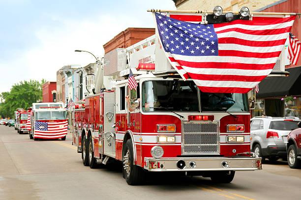 fire trucks with american flags at small town parade - geçit töreni stok fotoğraflar ve resimler