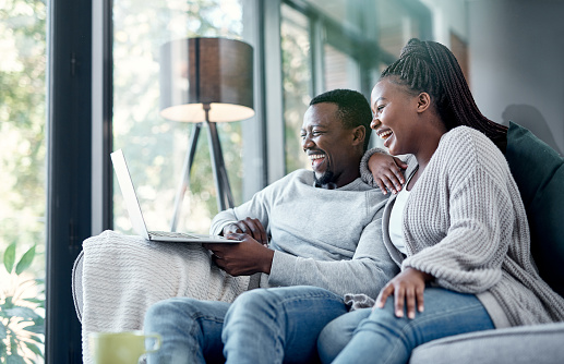 Shot of a young couple using a laptop together on the sofa at home