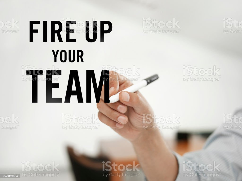 "businessman writing ""Fire up your team"" on a virtual board"