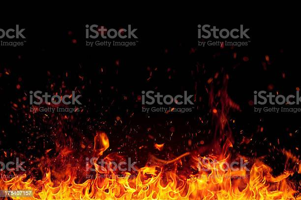 Photo of Fire with bright sparks isolated on black background