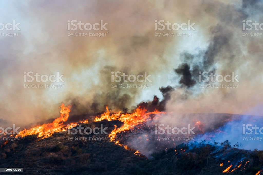 Fire with Orange Flames and Smoke on Hillside in California Woolsey Brushfire stock photo