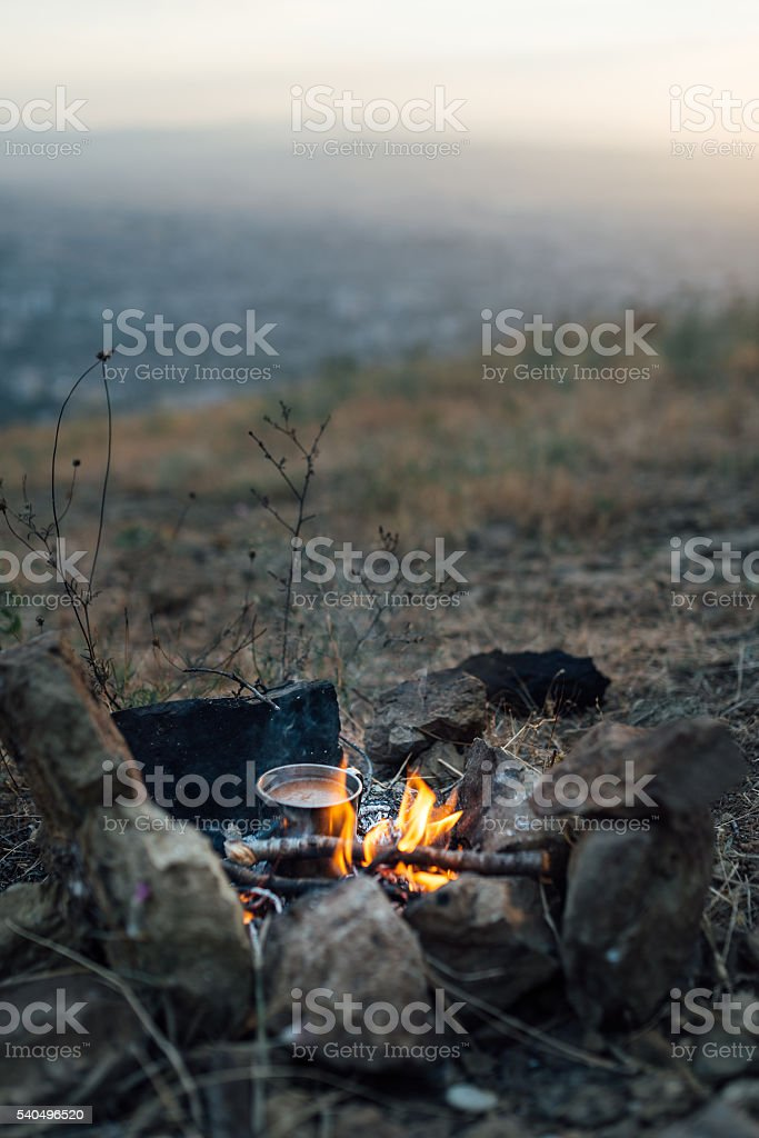 fire with  small pot of food stock photo