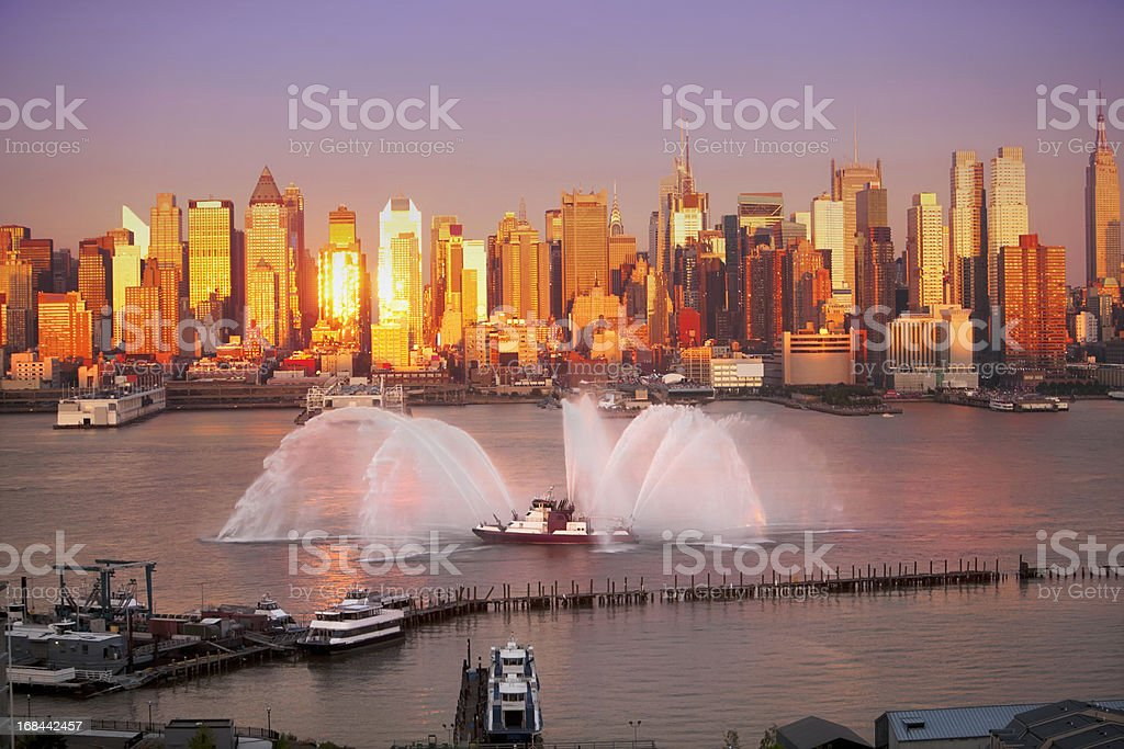 Fireboat at sunset New York City skyline stock photo