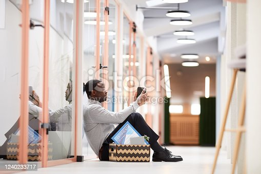 Full length side view at young African man sitting with box of belongings outside office after quitting job, copy space