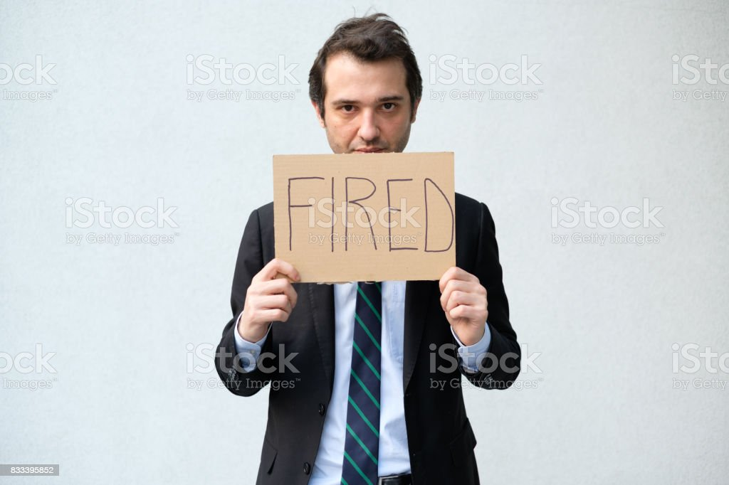 Fired businessman hiding his face with layoff message stock photo