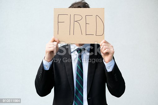 1181817161 istock photo Fired businessman hiding his face with layoff 910511564