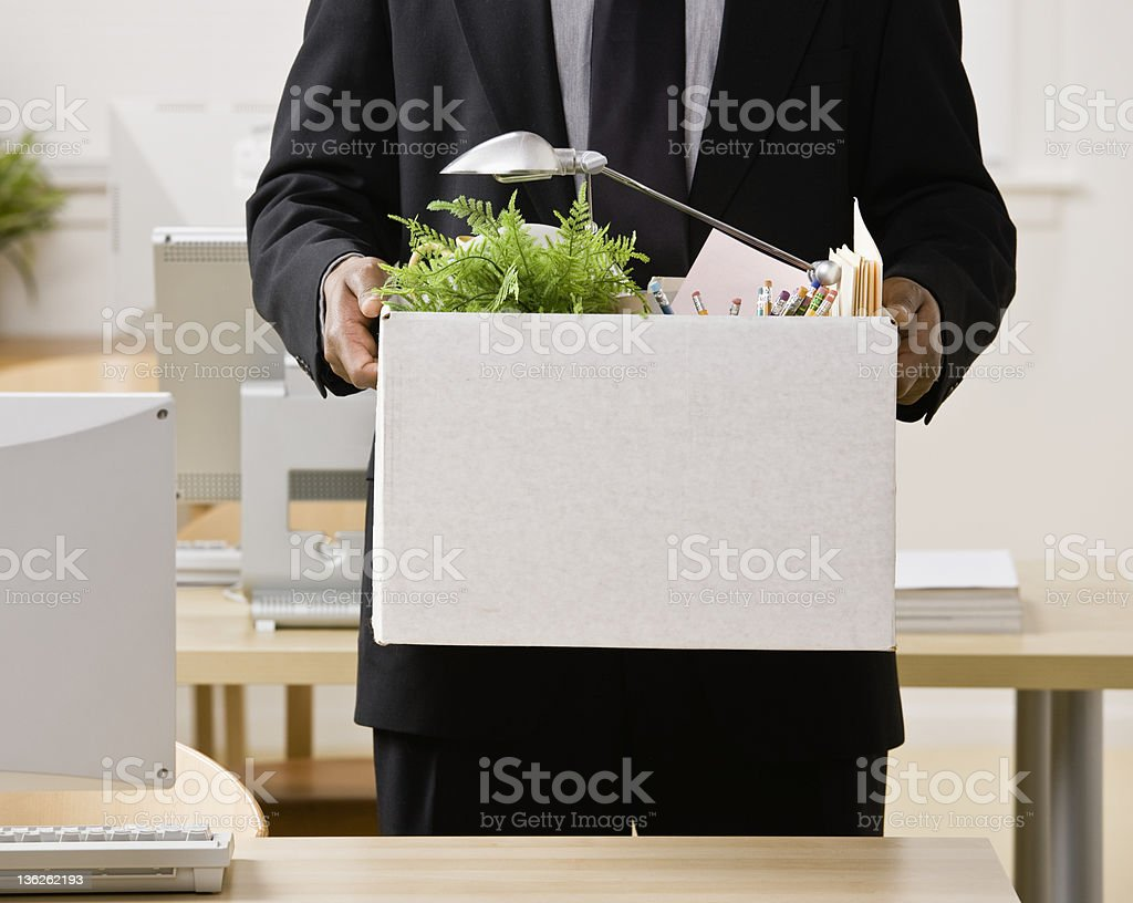 Fired businessman packing personal desk items in box stock photo