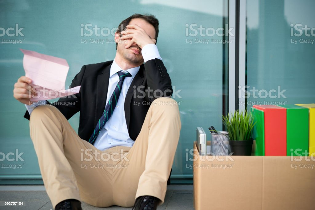 Fired businessman reading the notice of job termination stock photo