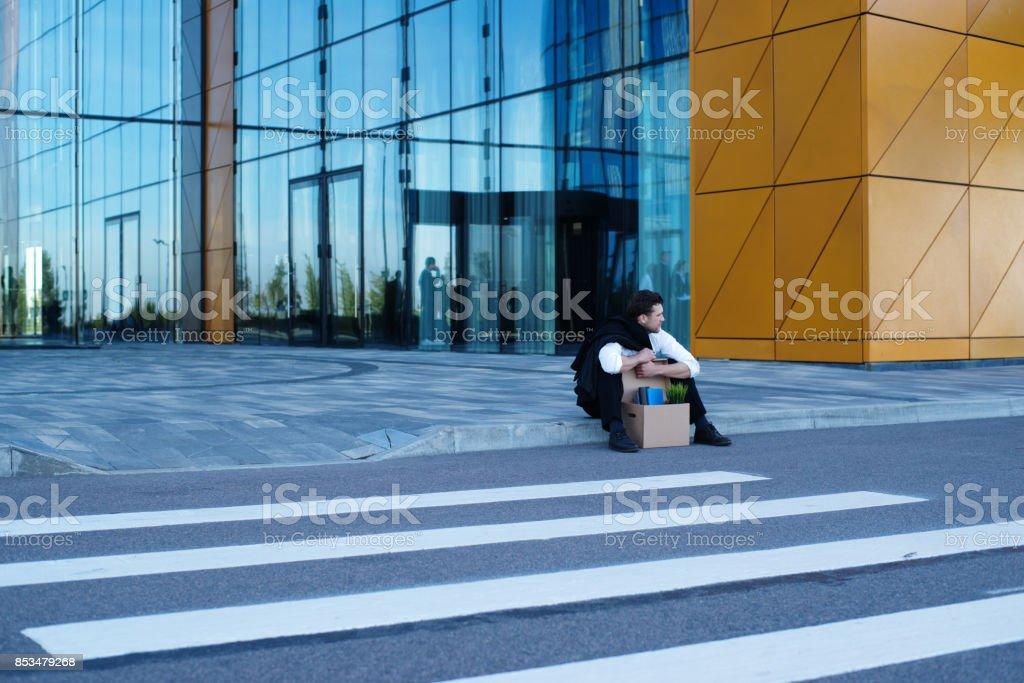 Fired businessman sitting on street stock photo
