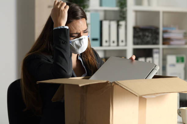 Fired executive with mask packing belongings at night stock photo