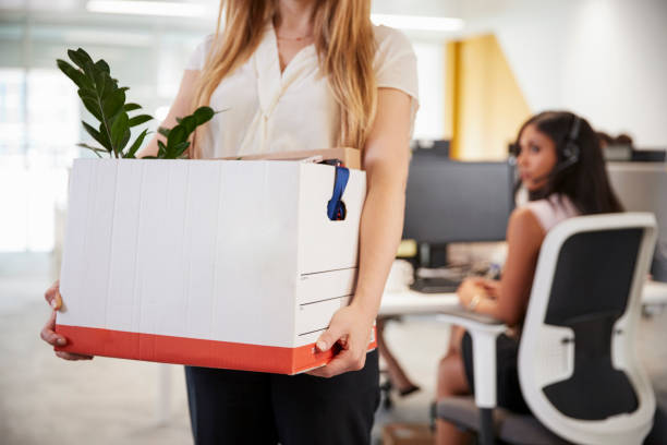 fired female employee holding box of belongings in an office - leaving stock photos and pictures